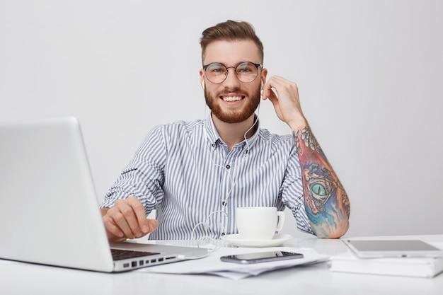 Porträt des entzückenden erfreuten bärtigen mannes mit der trendigen frisur hört audiospur mit kopfhörern