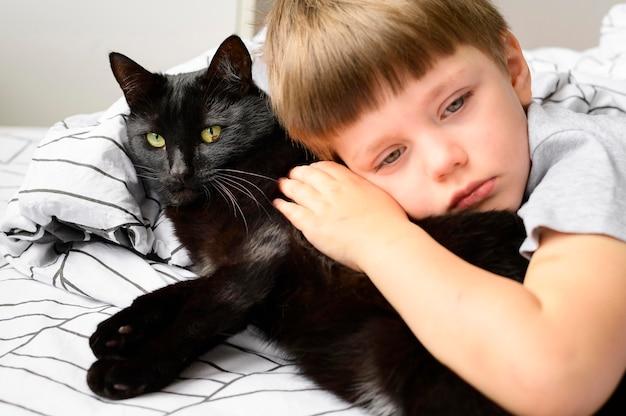 Porträt des entzückenden jungen, der seine katze umarmt
