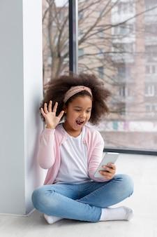 Porträt des entzückenden jungen mädchens, das mit ihrem telefon spielt
