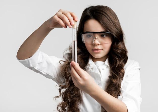 Porträt des entzückenden jungen wissenschaftlers, der chemieprobe prüft
