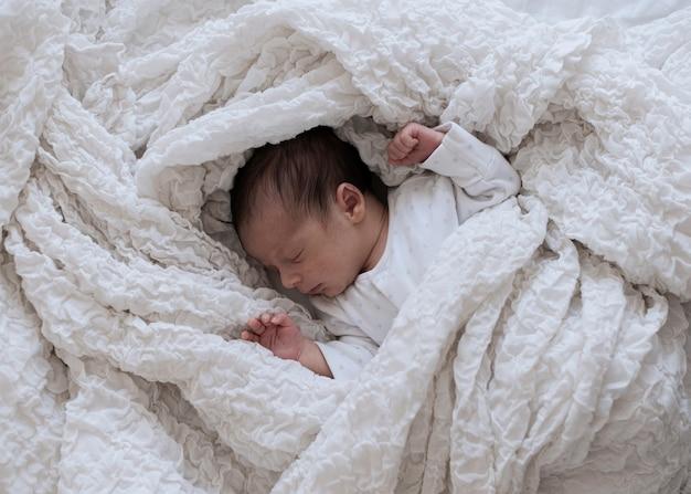 Porträt des entzückenden kleinen babys, das ein schläfchen hält