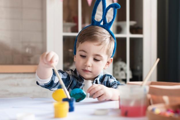 Porträt des entzückenden kleinen jungen, der eier für ostern malt