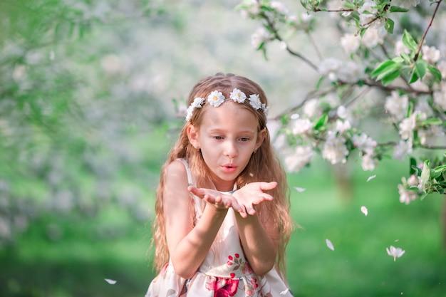 Porträt des entzückenden kleinen mädchens in blühendem kirschbaumgarten draußen