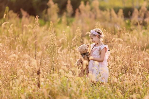 Porträt des entzückenden kleinen mädchens mit dem angefüllten teddybären im freien