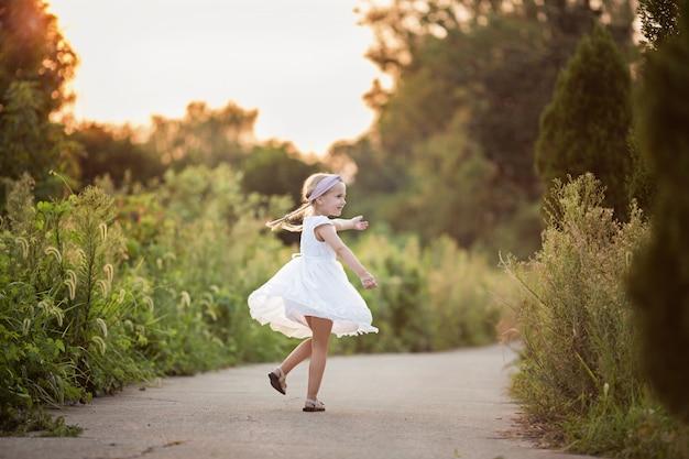 Porträt des entzückenden kleinen mädchens mit dem langen blonden haar im park