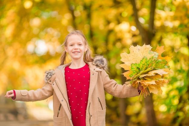 Porträt des entzückenden kleinen mädchens mit gelb lässt blumenstrauß im fall