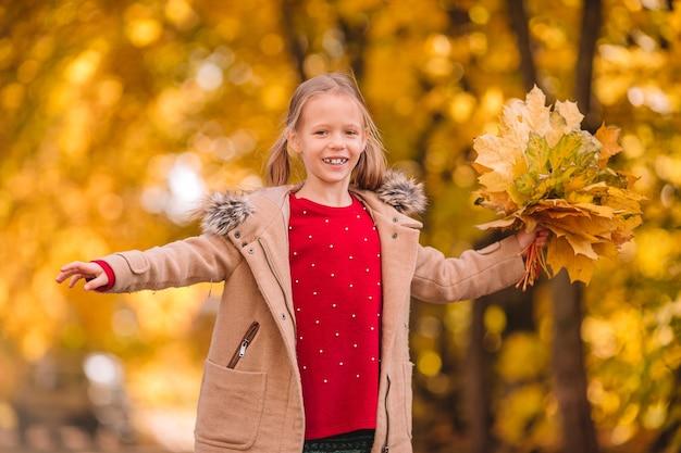Porträt des entzückenden kleinen mädchens mit gelbem blattstrauß im herbst