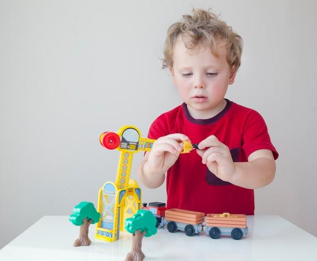 Porträt des entzückenden kleinkindjungen, der am tisch sitzt und mit einem hölzernen bauauto zu hause spielt. kleines kind mit spielzeugauto