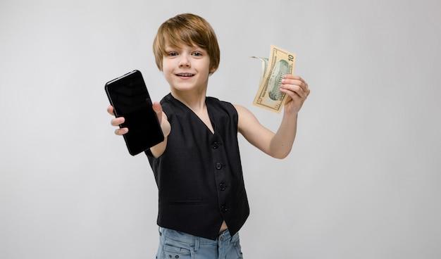 Porträt des entzückenden lustigen kleinen jungen, der in der schwarzen weste hält handy und geld auf grau steht