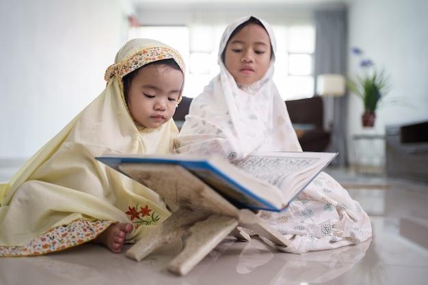 Porträt des entzückenden muslimischen jungen kindes las koran zusammen zu hause
