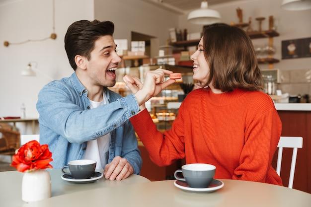 Porträt des entzückenden paares mann und frau, die in der gemütlichen bäckerei datieren und sich gegenseitig mit makronenplätzchen füttern