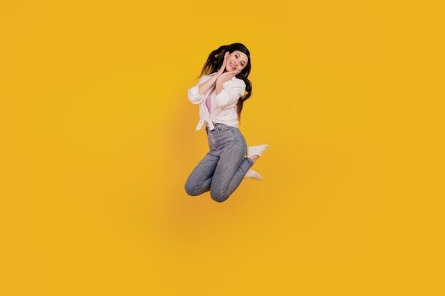 Porträt des entzückenden positiven mädchensprungs, der auf gelbem hintergrund aufwirft