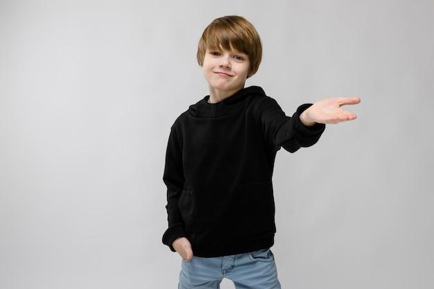 Porträt des entzückenden smilling kleinen jungen, der seine hand mit der hand in der tasche auf grau anbietend steht
