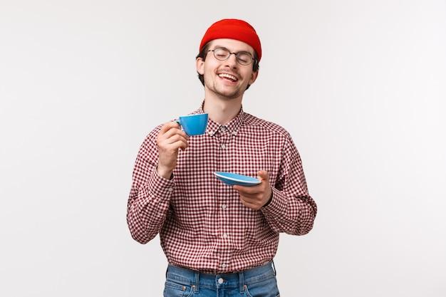 Porträt des entzückten entspannten und glücklich lächelnden hipster-kerls in den gläsern und in der roten mütze, die schöne tasse tee genießen, augen schließen und tasse als lob großen gebrühten kaffee, stehende weiße wand erheben