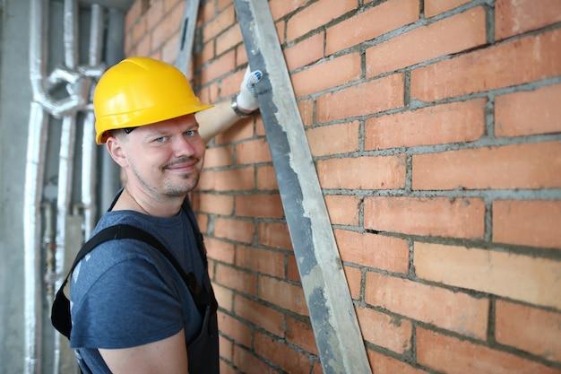 Porträt des erbauers backsteinmauer machend glatt, um backsteinmauer zu vergipsen. lächelnder baumeister in schutzkleidung, um traumata vorzubeugen. gebäudekonzept