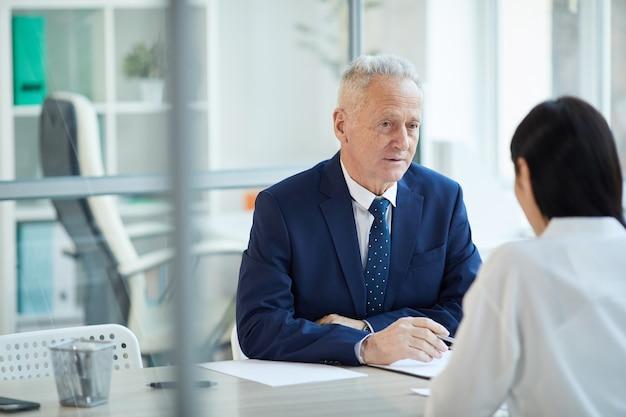 Porträt des erfolgreichen älteren geschäftsmannes, der junge frau für jobstelle im büro, kopierraum interviewt