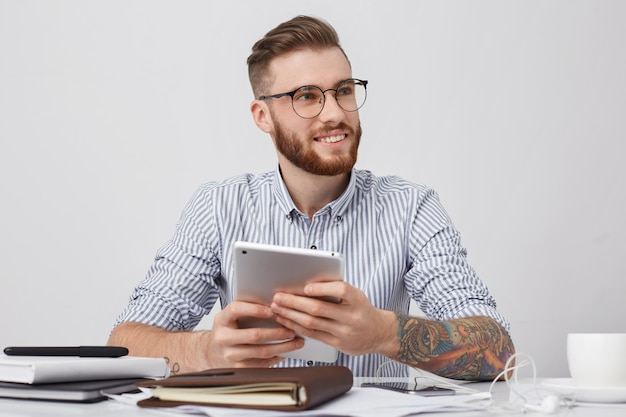Porträt des erfolgreichen büroangestellten in runden brillen, hat tätowierte arme, hält moderne tablette