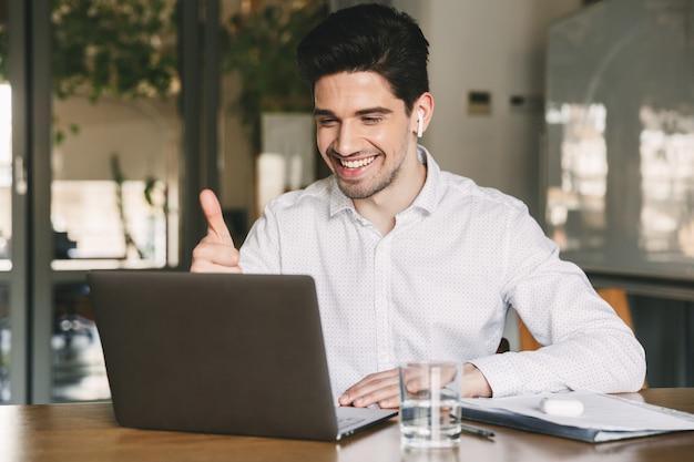 Porträt des erfolgreichen geschäftsmannes der 30er jahre, der weißes hemd trägt, das lacht und daumen oben am laptop im büro, während der videokonferenz oder des anrufs unter verwendung des bluetooth-ohrhörers zeigt