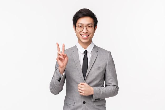 Porträt des erfolgreichen glücklichen und sorglosen jungen asiatischen geschäftsmannes im grauen formellen anzug, friedenszeichen zeigend und lächelnd, informieren unternehmensteam, das sie erfolgreich unterzeichnet haben, auf einer weißen wand