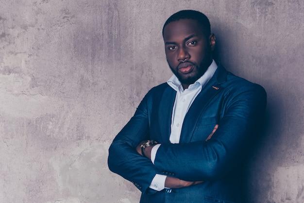 Porträt des erfolgreichen gutaussehenden afroamerikanischen mannes im stilvollen anzug gekreuzte hände
