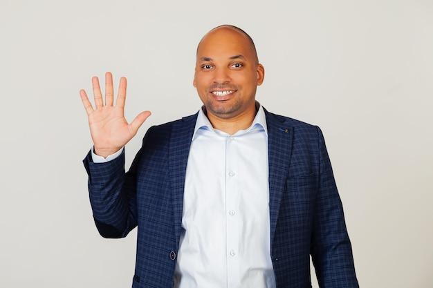 Porträt des erfolgreichen jungen afroamerikanischen geschäftsmannes, der mit den fingern nummer fünf zeigt, lächelnd, zuversichtlich und glücklich. der mann zeigt fünf finger. nummer 5.