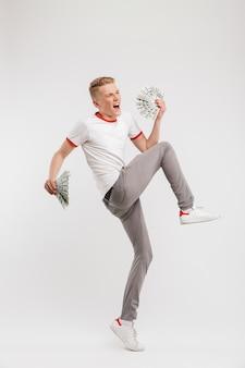 Porträt des erfolgreichen jungen mannes in voller länge, der lässige kleidung trägt, die mit zwei fans des auf weiß isolierten geldes schreit und springt