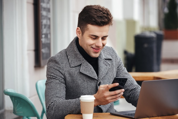 Porträt des erfolgreichen kerls stillstehend im straßencafé, arbeitend mit notizbuch und schreiben textnachricht an seinem handy
