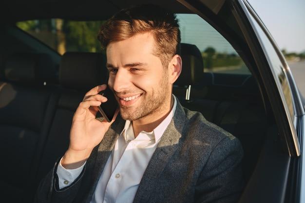 Porträt des erfolgreichen mannes im klassischen anzug, der auf smartphone spricht, während zurück im geschäftsklassenauto sitzt