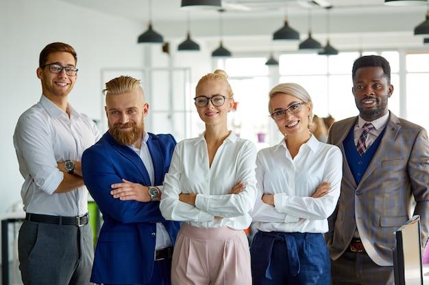 Porträt des erfolgreichen multiethnischen teams, das kamera im büro betrachtet