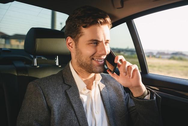 Porträt des erfolgreichen regisseurmannes im anzug, der auf smartphone spricht, während zurück im geschäftsklassenauto sitzt