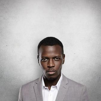 Porträt des erfolgreichen selbstbewussten dunkelhäutigen unternehmers, der grauen formellen anzug trägt und mit an der wand steht
