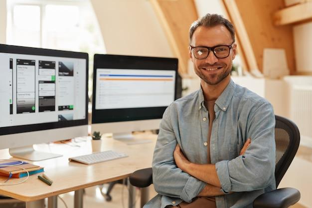 Porträt des erfolgreichen softwareentwicklers in brillen, die mit verschränkten armen stehen und an der kamera im büro lächeln