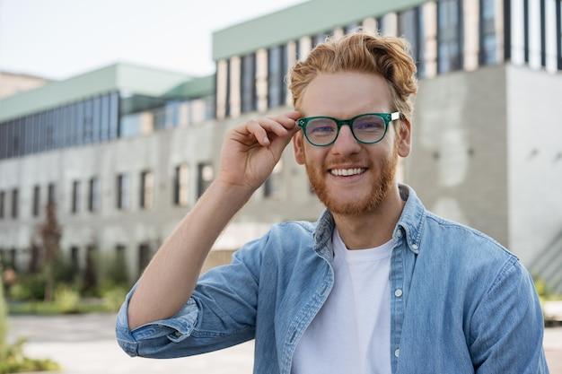 Porträt des erfolgreichen studenten, der kamerabildungskonzept betrachtet