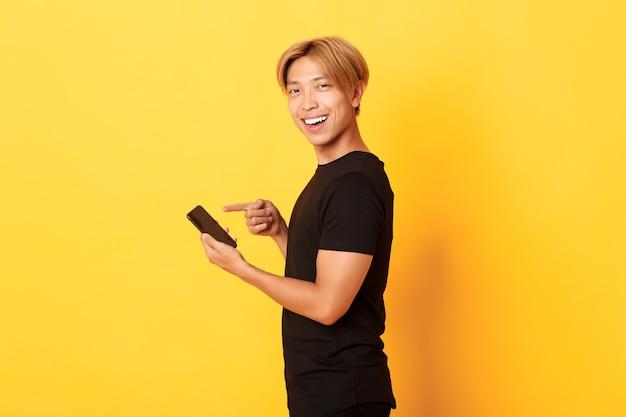 Porträt des erfreuten lächelnden gutaussehenden asiatischen mannes, der im profil steht und finger auf smartphone zeigt, app empfehlen, gelbe wand stehend