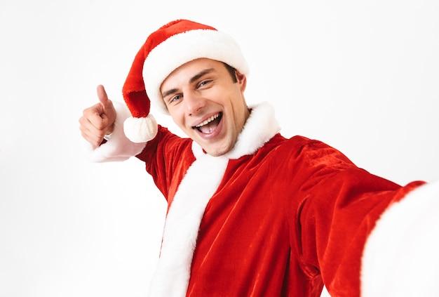 Porträt des erfreuten mannes 30s im weihnachtsmannkostüm und im roten hut, der lacht, während er selfie-foto macht