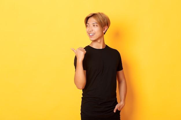 Porträt des erfreuten nachdenklichen asiatischen kerls, der schaut und zeigt finger links auf logo, stehende gelbe wand