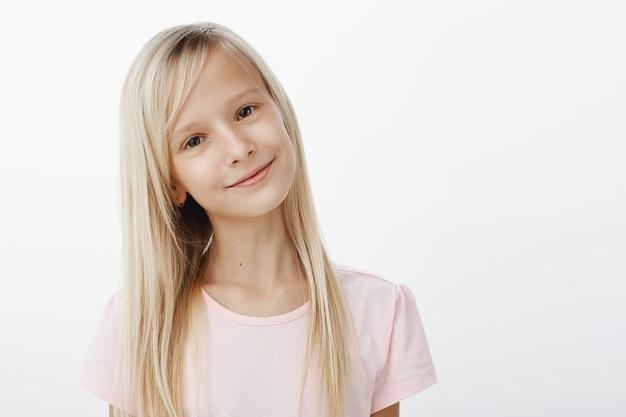 Porträt des erfreuten positiven niedlichen kindes mit glücklichem zufriedenem lächeln, neigendem kopf, während man genau zuhört, gutes gehorsames kind ist, das über grauer wand steht
