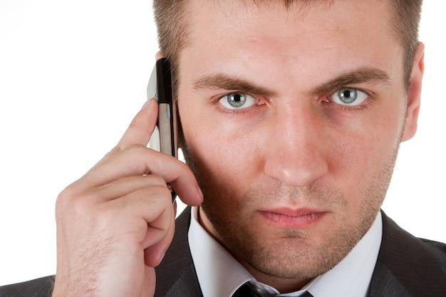 Porträt des ernsten geschäftsmannes mit telefon