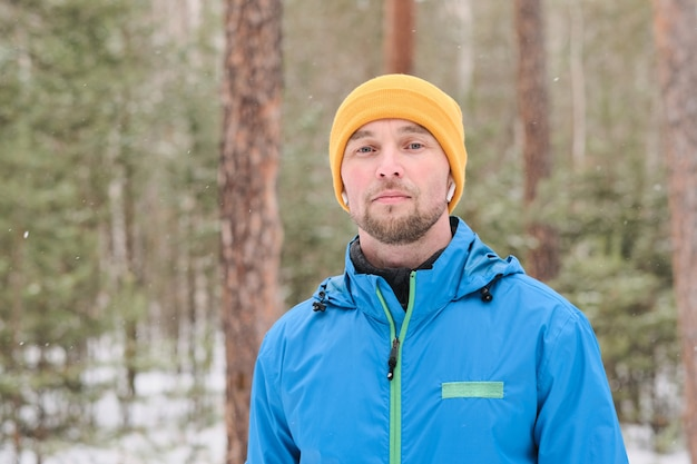 Porträt des ernsten gutaussehenden jungen mannes in den ohrknospen, die im winterwald stehen