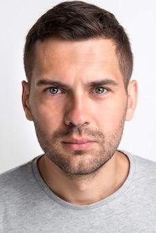 Porträt des ernsten gutaussehenden mannes kamera gegen weißen hintergrund betrachtend