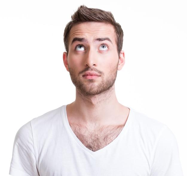 Porträt des ernsten hübschen jungen mannes, der oben schaut - lokalisiert auf weiß.
