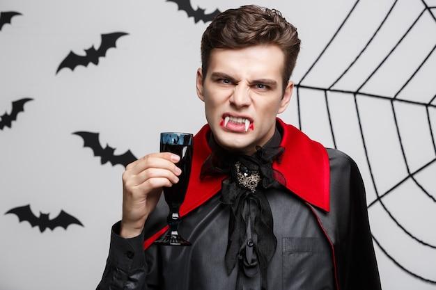 Porträt des ernsten hübschen kaukasischen vampirs genießen, blutigen rotwein zu trinken.