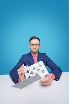 Porträt des ernsten intelligenten jungen bärtigen kartenspielers in den gläsern, die am tisch sitzen und karten werfen