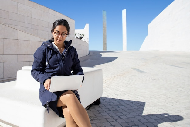 Porträt des ernsten jungen freiberuflers, der draußen an laptop arbeitet
