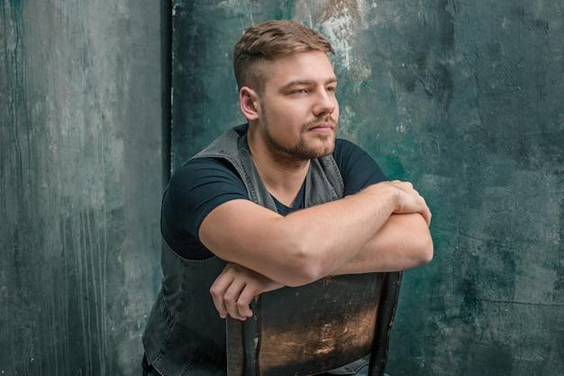 Porträt des ernsten mannes, der auf dem holzstuhl auf grauem studio sitzt