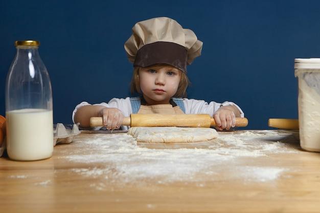 Porträt des ernsten niedlichen weiblichen kindes des vorschulalters, das an der küchentheke trägt kochmütze steht