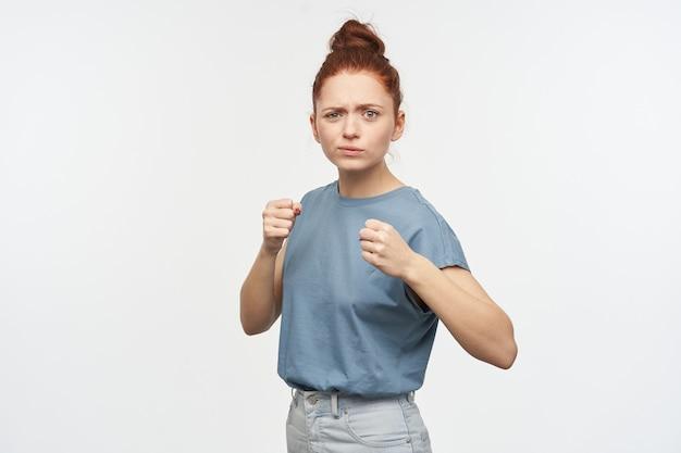 Porträt des ernsten rothaarigen mädchens mit den haaren, die in einem brötchen gesammelt werden. trage ein blaues t-shirt und jeans. ballen sie die fäuste. steh in kampfhaltung. isoliert über weiße wand