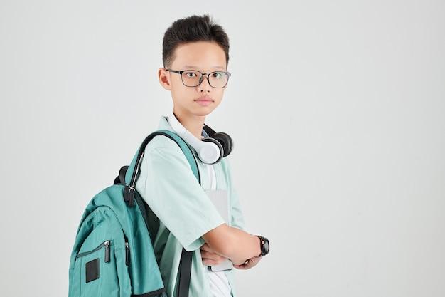 Porträt des ernsten vietnamesischen schülers in den gläsern, die mit rucksack, kopfhörern und tablet-computer aufwerfen