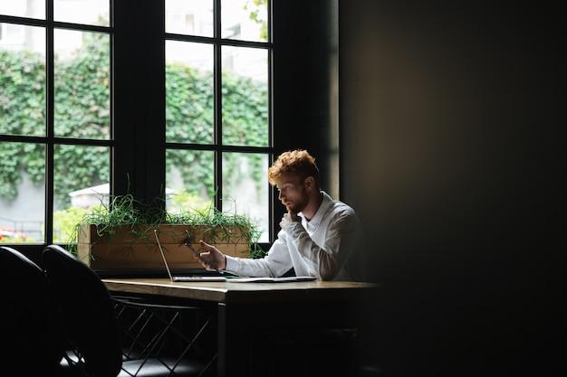 Porträt des ernsthaften bärtigen bärtigen geschäftsmannes, der smartphone hält und am arbeitsplatz sitzt