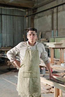 Porträt des ernsthaften gutaussehenden zimmermanns mittleren alters in der schutzbrille, die am schreibtisch in der werkstatt steht